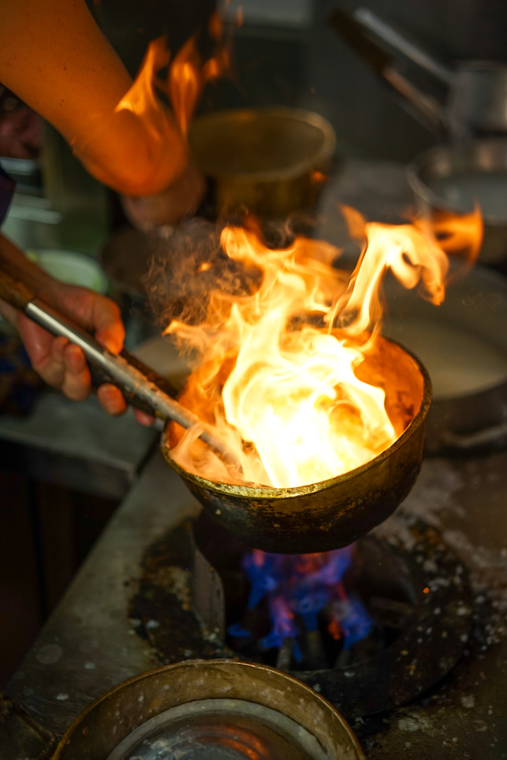 Traditional copper pots are used and the fish is flambeed in Mui Kee's signature dish. (Photo credit: Rex Chapman)